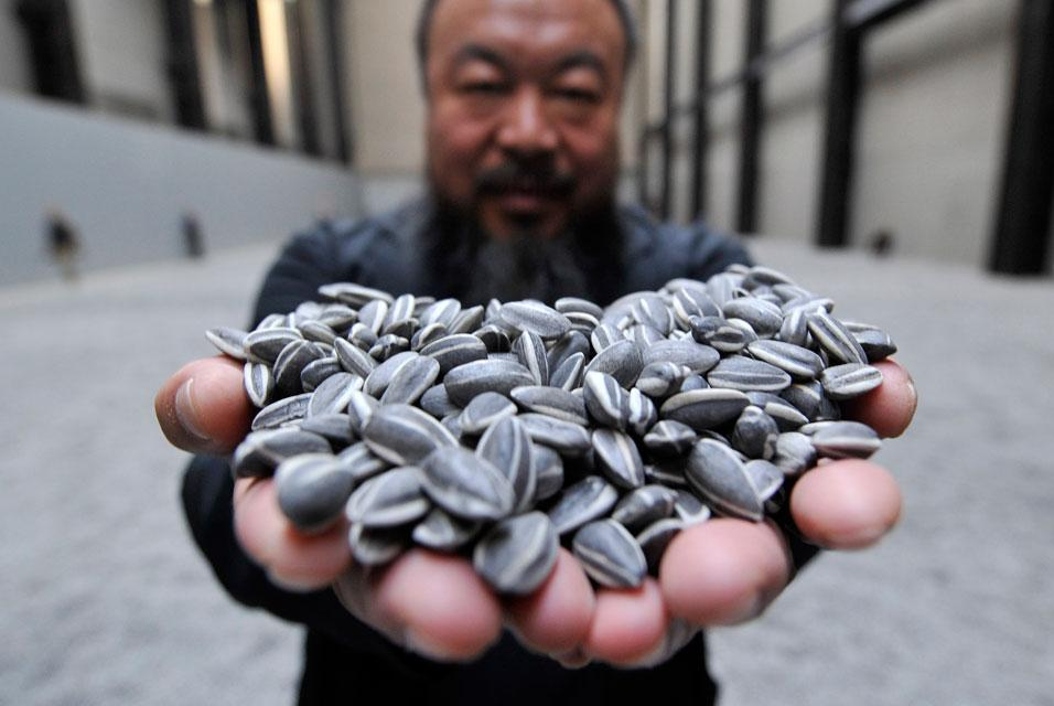 Ai Wei Wei holds a small handful of the thousands of handmade porcelain sunflower seeds in his exhibition. The artist immigrated to Germany, and opened a large shop in Berlin.